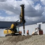 EXCAVATOR MOUNTED DRILL RIG NEAR WALL